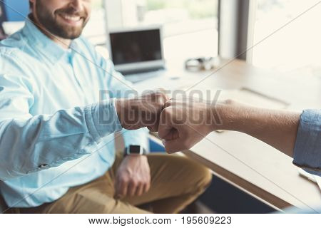 Close up of hands of cheerful young bearded man with toothy smile sitting next to his colleague at table. He bumping friendly his fist by own fist