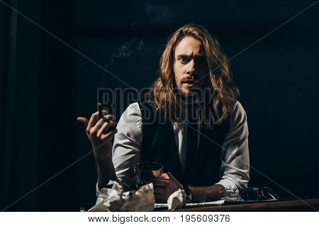 Bearded Handsome Long Haired Man In Formal Wear Smoking Cigar While Holding Glass Of Whisky And Look