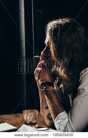 Handsome Young Bearded Man Smoking Cigar While Sitting At Table With Glass Of Whisky