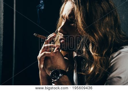Close-up Portrait Of Pensive Bearded Young Man Smoking Cigar And Looking Away