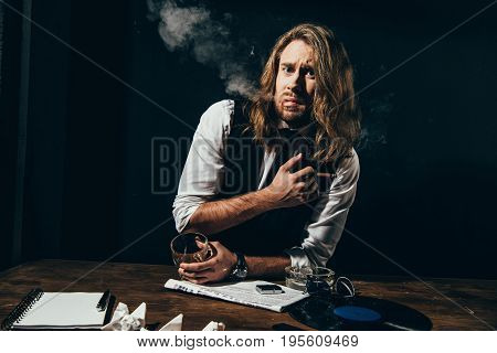 Handsome Stylish Young Man In Formal Wear Drinking Alcohol And Smoking Cigar Indoors