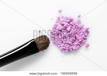 Broken pink eye shadow and brush isolated on the white background