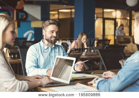 Portrait of happy bearded man sitting with two colleagues at one table in open space room and discussing job issues with interest. Blonde lady is typing on laptop. Guys are holding pens in hands
