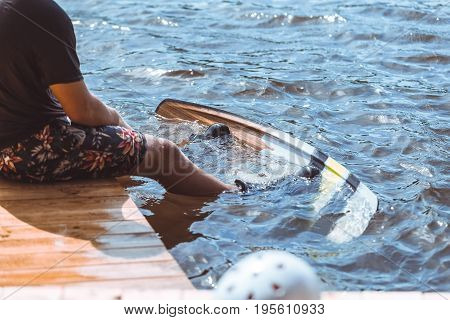 Summer time wake board extreme water sports concept. Man standing on jetty peer on a lake river with feet in wakeboard ready to go wakeboarding. Vacation, holiday getaway fun with friends and family