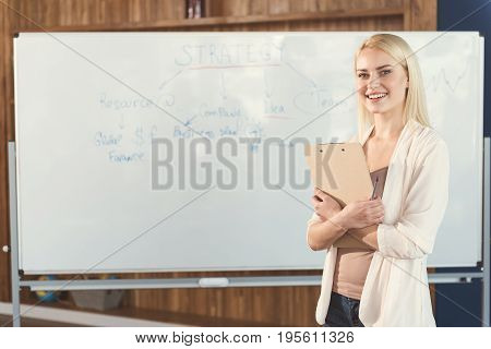 Waist up portrait of jolly young lady standing with her back to huge flipchart and smiling broadly. She is cuddling clipboard and holding pen in one hand. Copy space in left side
