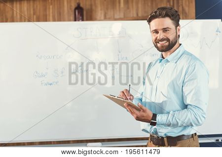 Waist up portrait of happy young man with beard standing with his back to flipchart and smiling. He is holding clipboard and pen in hands. Copy space in left side