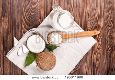 Tasteful tropical coconut milk in a mason jar with a fresh coconut and wooden spoon with nut chips on a light fabric and on a dark wooden background. Nutritious cracked nuts, top view.