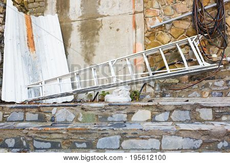Old wooden ladder lying on a gravel path, leaning up against an old stone wall.