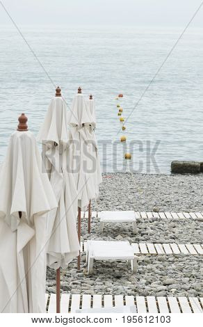 Sea beach pebbles umbrellas sunbed access to the sea. Rest on the sea travel