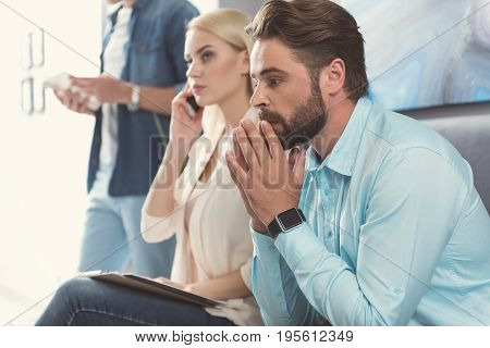 Thoughtful young man with beard is sitting in queue next to other applicants. He is keeping palms together near his lips as if praying. Serious blonde girl next to him is talking via cellphone