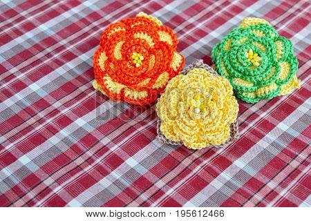 Crocheted multicolored flowers. Decorated flowers idea. Beautiful crafts