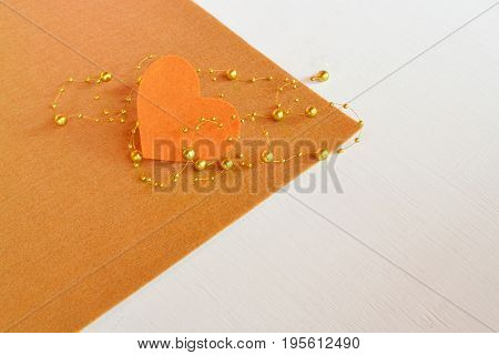 Felt heart with beads on a brown felt sheet. Heart background