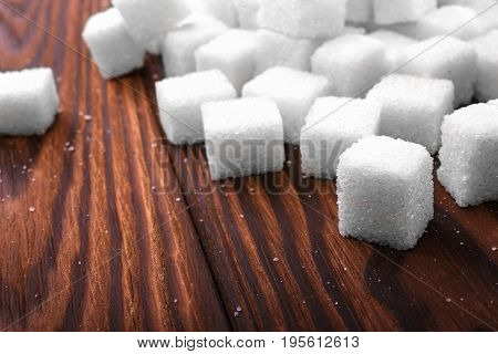 Sweet sugar cubes on a dark wooden table. A pile of white lumps of sugar cubes for cooking, baking, drinks and beverages. The health risks related to calorie intake.