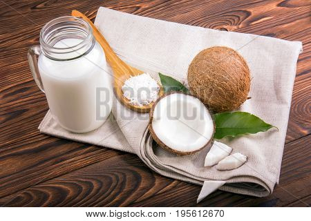 Fresh and organic products from coconuts. Tropical nut milk in a mason jar with fresh coconuts with green leaves and wooden spoon with coco chips on light fabric and on a dark wooden background