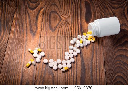 White and yellow different pills, tablets, vitamins, and drugs scattered near an opened white medicine bottle on a wooden background. Treatment with pills and medicine.