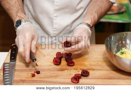 Chef is removing stones from cherry in professional kitchen