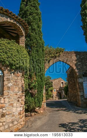 Les Arcs-sur-Argens, France - July 10, 2016. View of stone wall and arch at the entrance of the gorgeous medieval hamlet of Les Arcs-sur-Argens. Provence region, Var department, southeastern France