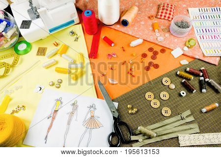 Workplace of a dressmaker: scissors buttons spools measuring tape sketches fabric needles sewing machine and other tools.