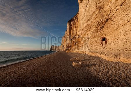 The pebbled beach and natural arch Porte d'Amont of Etretat, a commune in the Seine-Maritime department in the Normandy region of north western France