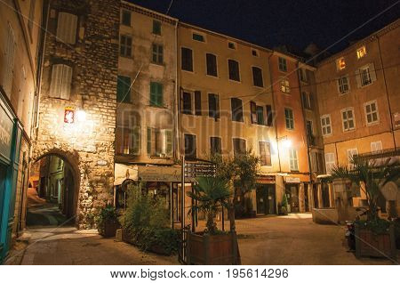 Draguignan, France - July 10, 2016. Night view of arch and square with buildings and light of lanterns, in the pleasant city of Draguignan. Provence region, Var department, southeastern France