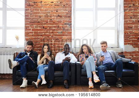 Diverse Group of People Community Togetherness Technology Sitting Concept