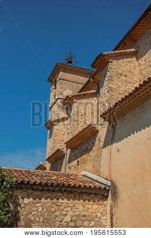 View of side wall and church steeple in the morning sun with blue sky in the calm and charming village of Figanières. Located in the Var department, Provence region, southeastern France