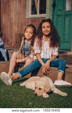Multiethnic Girls Sitting On Porch With Cute Labrador Puppy