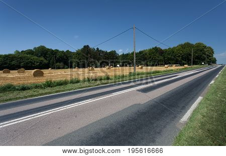 A repaired and pot hole free country road alongside a field of hay bales in Normandy, France