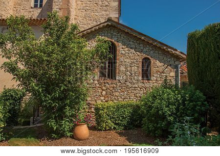 View of little house with bushes in the morning sun with blue sky, in the quiet and charming village of Figanières. Located in the Var department, Provence region, southeastern France
