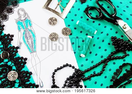 Workplace of a dressmaker: buttons spools scissors sketch buckle fabric lace and beads