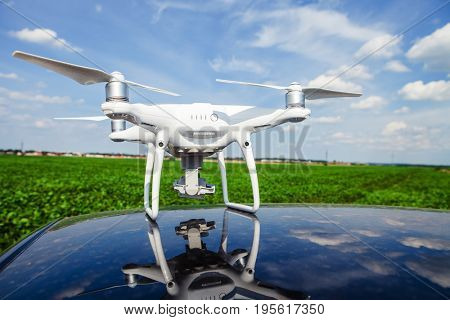 drone on the roof of car on a background the green field