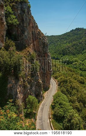 View of green valley and cliff, cut by road, near Châteaudouble, a quiet and tourist village with medieval origin on a sunny day. Located in the Var department, Provence region, southeastern France