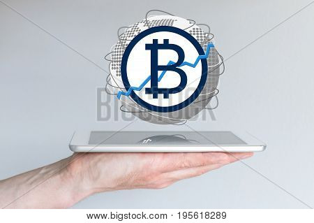 Increasing of global bitcoin currency exchange rate concept with hand holding tablet