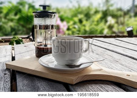 French press coffee maker and cup studio lit on table with nature background
