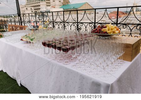 Wineglasses and fruit plate on the table with white cloth for the wedding catering