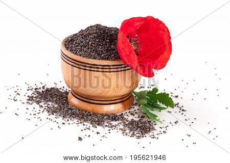 Poppy seeds in a wooden bowl with a flower.