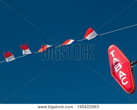 Editorial Les Loges, France - July 07, 2017: French flags erected ready to celebrate Bastille Day (Fête Nationale) and a Tabac sign sign indicating a retail outlet for cigarettes and tobacco seen in the village of Les Loges, Normandy.