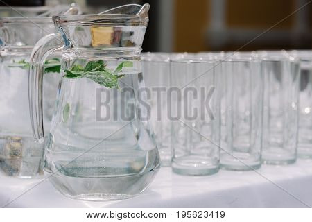 Jug with water and mint leaves next to the empty glasses