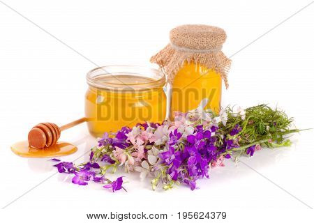 Jar of honey with wildflowers isolated on white background.