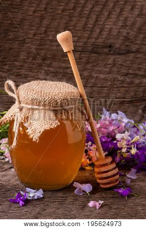 Jar of honey with wildflowers on old wooden background.