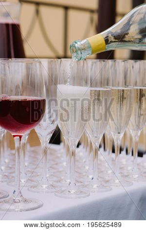 Poured wineglasses with red wine and champagne on the table for the wedding catering