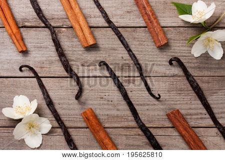Vanilla sticks and cinnamon with flower and leaf on a old wooden background.