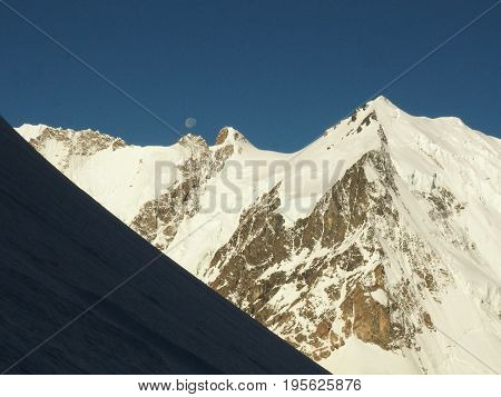 The view of north face of mount Dykh Tau in morning sunlight with a clear summit, in the mountains of the Russian Caucasus