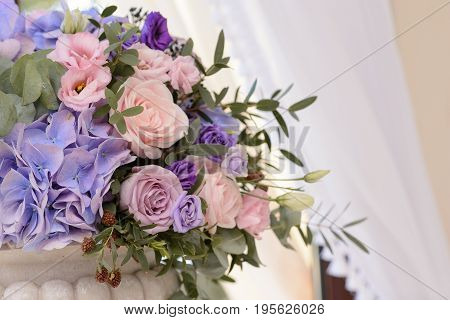 Floral decoration with the violet, blue, pink flowers and greenery for the wedding ceremony