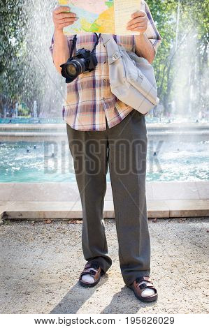 Senior tourist man with camera and map socks and sandals