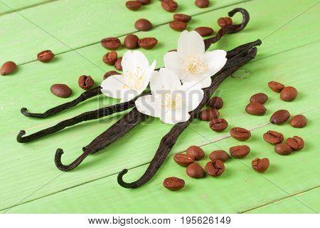 Vanilla sticks and coffee beans with flower and leaf on a green wooden background.