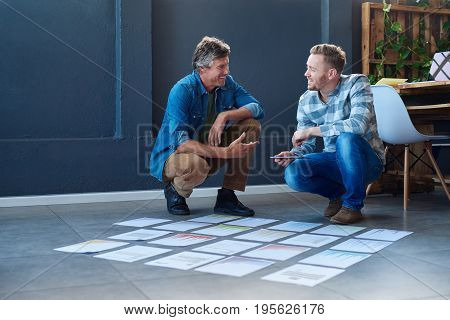 Two smiling young office colleagues brainstorming together while crouching over paperwork spread out in a square on the floor of a modern office