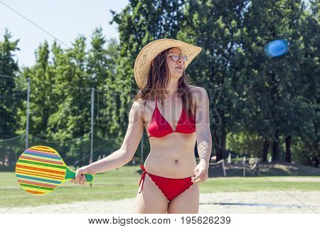 Young Adult Woman Playing Tennis On The Beach