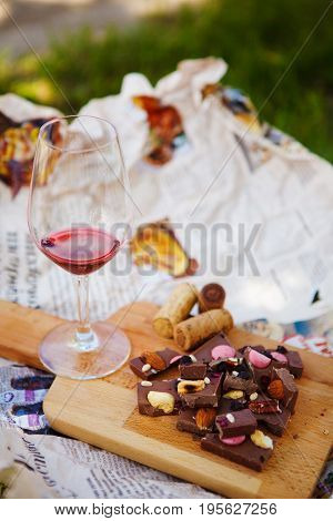 Glass with red wine and pieces of chocolate with nuts and raisins stands on cutting board on background of newspapers on the ground outdoors. Alcoholic drink in glassware with snacks