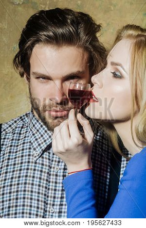 Macho and girl posing with glass of red liqueur. Pretty woman with blond long hair and handsome man on beige background. Couple in love. Alcohol and appetizer. Unhealthy lifestyle and bad habits